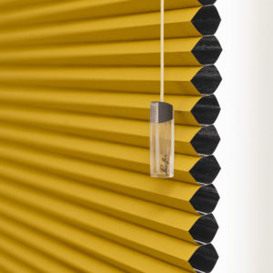 blackout duette blind in yellow and black colour with honeycomb structure and hand cord.