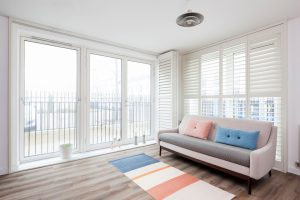 full height Fiji Shutters on tracked system fully opened in living room
