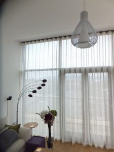 Wave curtains with white translucent fabric over large apartment window.