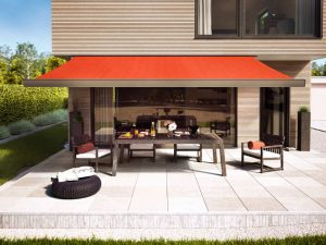 Markilux awning 970 model over outdoor patio area with red fabric style.