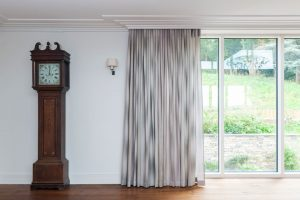 wave curtains with grey fabric across French sliding doors in living room area.