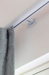 Wall fixed curtain track with face fixed bracket holding grey curtain.
