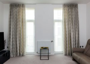 Tracked curtains with wave design in neutral living room.