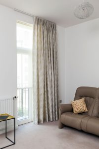 Top fix curtain track holding curtains in living room windows.