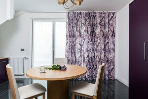 Irish linen curtains in purple fabric covering large window in dining room area.