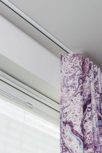 Irish linen curtain fabric in purple self heal colour attached to top fixed curtain track.