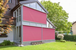 Vertical external blinds covering main large windows of wooden home.