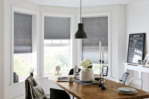 grey blinds in bay window in dining room.
