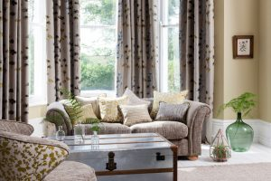 Traditional curtains in brown grey fabric with blue and yellow floral pattern in living room window.