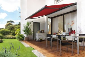 Awning extended over wooden patio area in colourful garden.