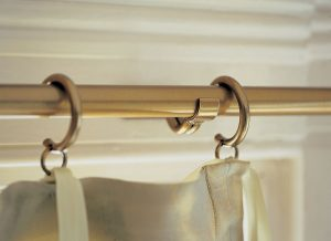 Brass rings on brass curtain pole holding curtains.