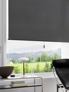 Charcoal roller blind with central hand cord in office.