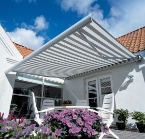 Markilux 990 Awning extended over sunny garden patio.