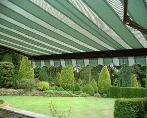 Awning extended over patio with traditional green striped pattern.