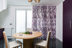 Irish linen curtains with purple Torrent pattern across French Doors in contemporary dining room area.