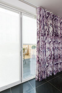 Curtains in purple river pattern hanging on top fix track hanging over French Doors with LiteRise® blind opened in window.