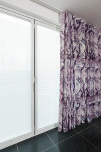 Designer curtains on top fix track hanging over French Doors and with LiteRise® blinds in windows.