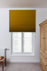 Luxaflex® Duette® Shades in Yellow design blind half closed across top half of bedroom window.