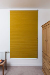 Duette blackout blind in yellow design fully closed in bedroom window.
