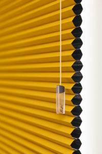 Yellow Luxaflex® Duette® Shades fully closed showing open honeycomb structure. and SmartCord