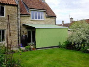 Markilux awning with retractable valance pulled down in garden patio area.