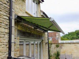 Markliux awning side profile in classic striped green colour over garden patio.