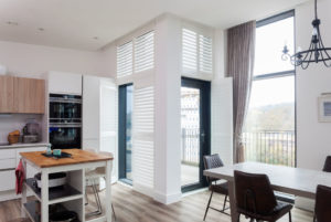 S-craft full height shutters in large kitchen corner window with open panels revealing balcony area.