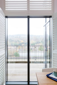 Full height shutters on French doors fully open leading to balcony area.