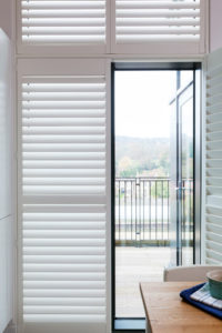 Full height Shutters on French doors opened and leading to balcony area.