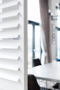 Wooden shutters panel open in kitchen area.