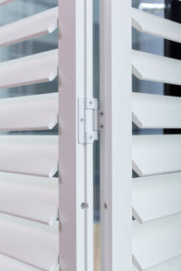 Shutters metal hinges between shutter panels in white finish.