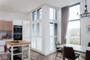 wooden full height shutters in white finish with opened slats in kitchen corner window.