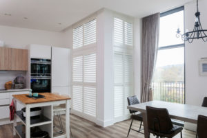 White wooden full height shutters with closed slats in kitchen corner window.