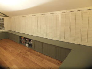 Multiple panels of full height wooden shutters with slats closed in large porch area.