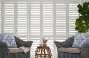 Security shutters in living room interior window behind wicker chairs.