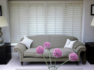 Off white wooden shutters with closed slats in large window behind grey contemporary sofa.
