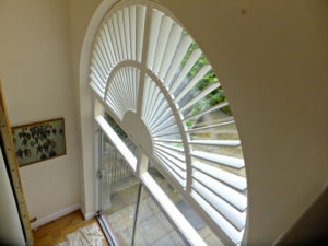 Shaped custom wooden shutter in large arched window above glass sliding doors.