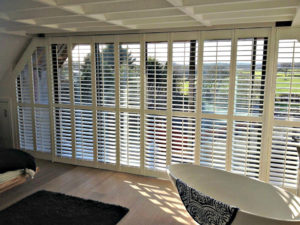 Wooden shutters in large sunny roof room window.