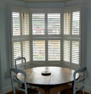 White wooden shutters in bay window in dining room.