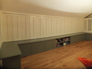 Full height wooden shutters above olive green cupboards in large porch.