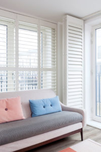 White full height shutters with open slats behind grey contemporary sofa.