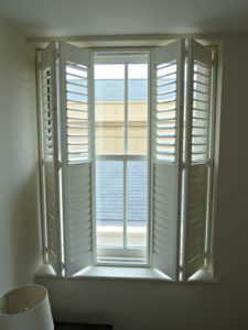 Full height off white wooden shutters opening on tracked system in bedroom side window.