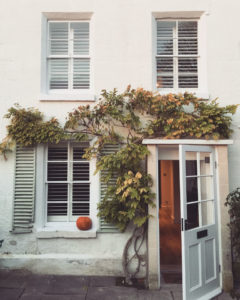 Exterior shot of house with white wooden shutters in windows.