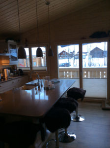 Plisse shades in bottom up position in wood cabin kitchen windows with snowy mountain view.