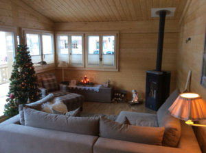 Plissé Shades in wooden cabin living room windows and wood fire chimney feature.