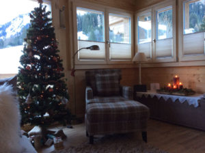Plissé Shades in wood cabin with armchair and Christmas decorations.