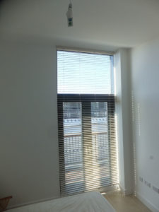 Venetian blinds with opened slats over balcony door window in bedroom.