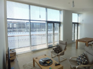 Metal venetian blinds fully opened in neutral tone contemporary penthouse apartment.