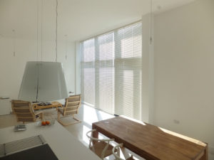 Metal venetian blinds with slats closed in large window in neutral contemporary apartment.