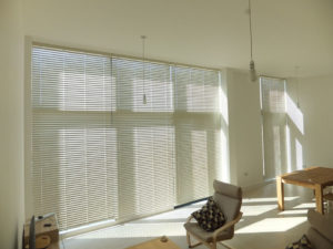 Metal venetian blinds closed in neutral tone contemporary penthouse apartment.